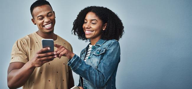 African American Man and Woman Reading Phone and Smiling